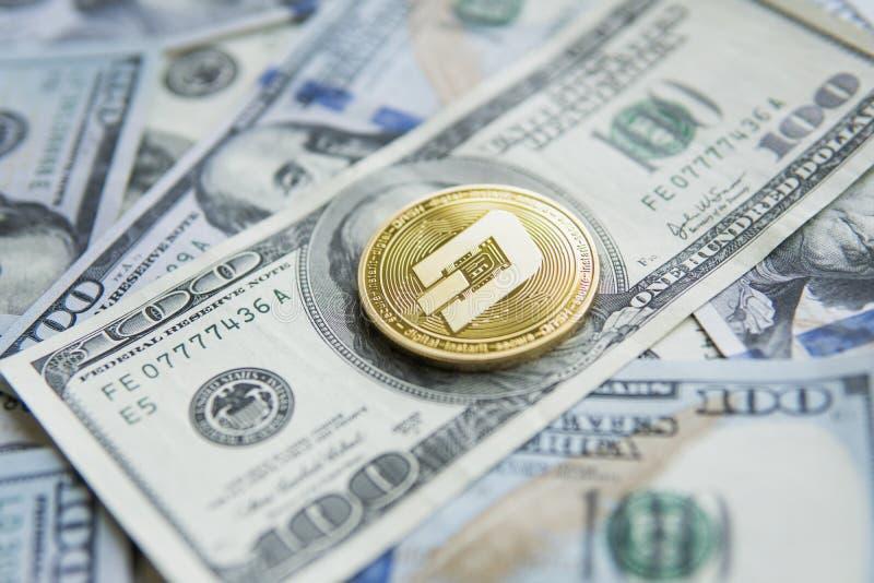 Guld- streckCryptocurrency mynt på en hög av US dollar, kontanta pengar och det crypto valutabegreppet faktiskt Metallmynt av royaltyfria foton
