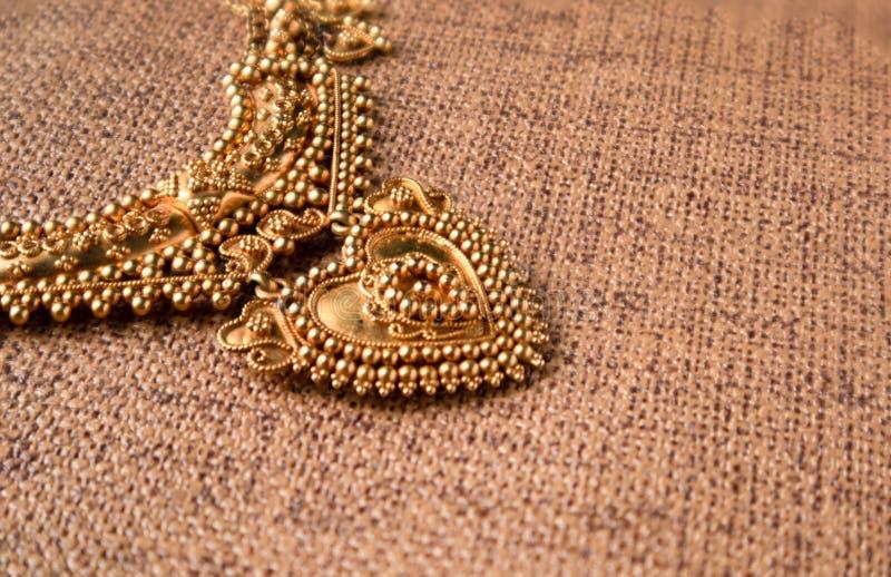 Guld- tättsittande halsbandhalsband med gemstones traditionella indiska gifta sig smycken på trätexturerad bakgrund royaltyfri fotografi