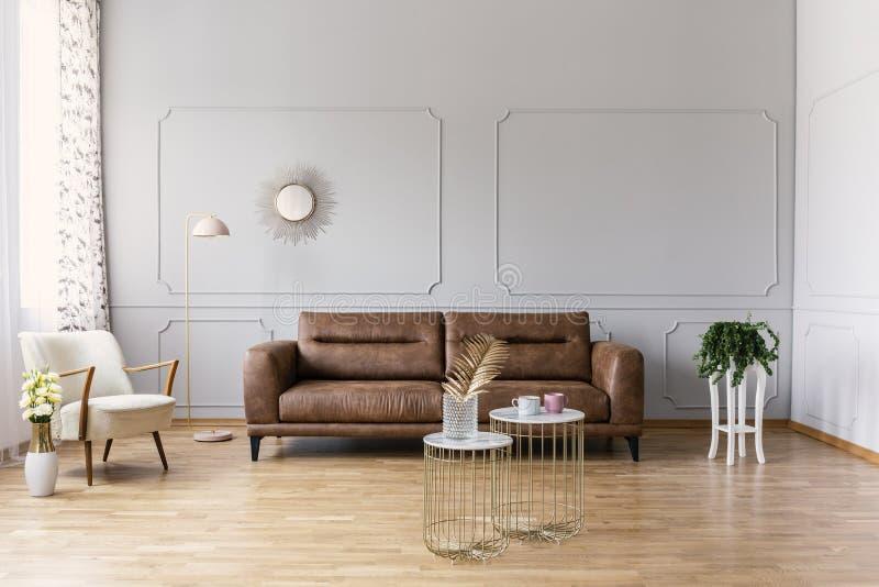 Guld- tabeller av lädersoffan i grå färger sänker framme inre med gula blommor och fåtöljen arkivfoton