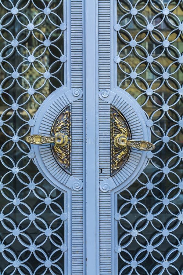 Guld- tappningdörrhandtag på dekorativa dörrar för exponeringsglas och för blåttmetall i bulgarisk slott royaltyfri fotografi