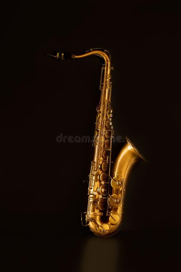 Guld- tenorsaxofon för Sax i svart arkivbilder