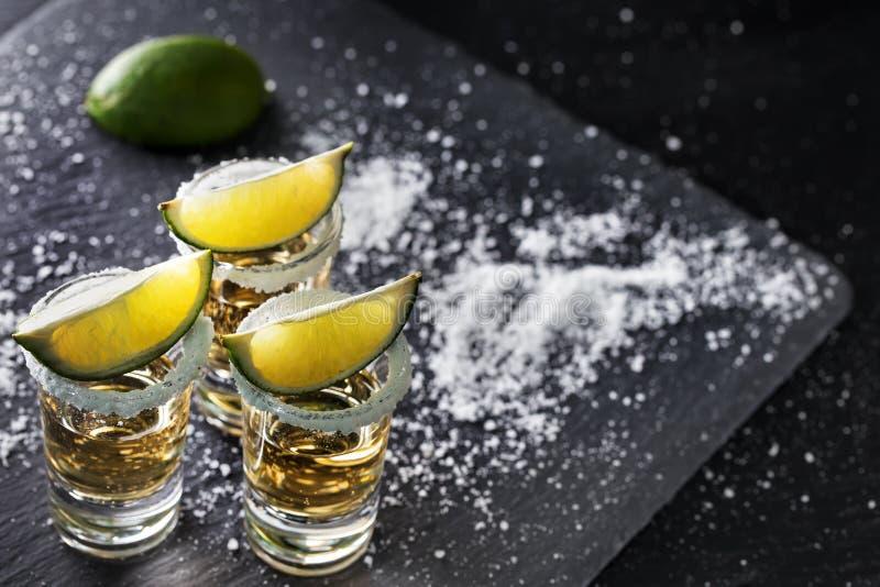 Guld- tequila på en svart bakgrund fotografering för bildbyråer