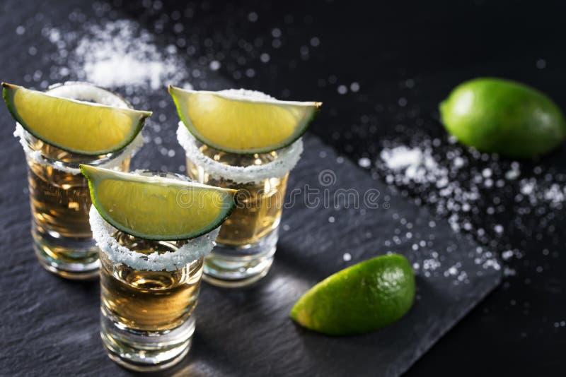 Guld- tequila på svart bakgrund royaltyfria foton