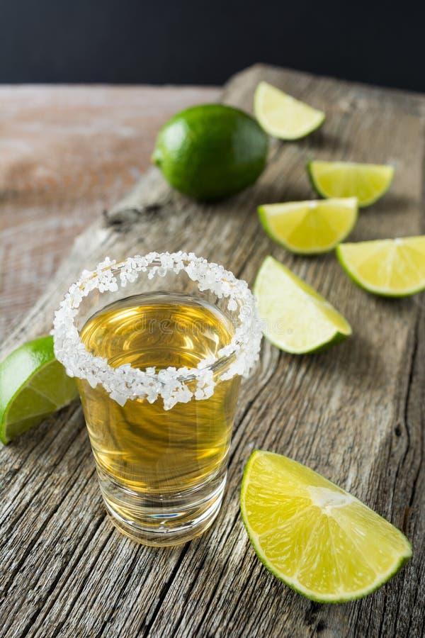 Guld- tequilaskott med limefruktskivor på den lantliga trätabellen royaltyfri fotografi