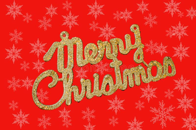 Guld- text för glad jul på en röd bakgrund med snöflingor vektor illustrationer