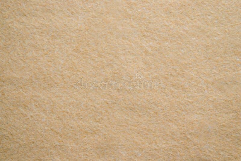 Guld- texturbakgrundspapper i gul tappningkräm eller beige färg, pergamentpapper, abstrakt pastellfärgad guld- lutning royaltyfri foto