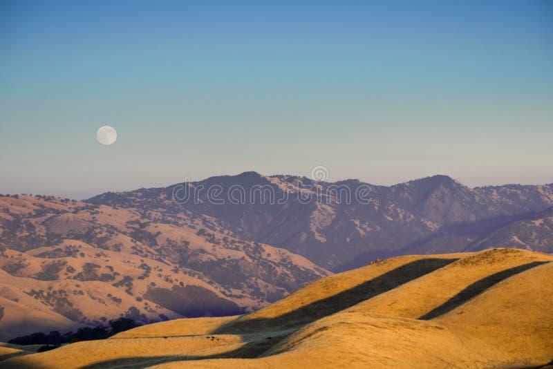 Guld- timme och fullmåne som stiger över kullarna och dalarna av Ohlone den regionala vildmarken royaltyfri foto