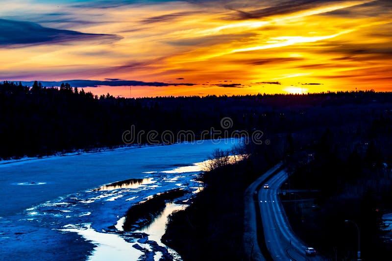 Guld- timmesolnedg?ng ?ver den djupfrysta floden Vinter i Edmonton, Alberta, Kanada arkivfoton