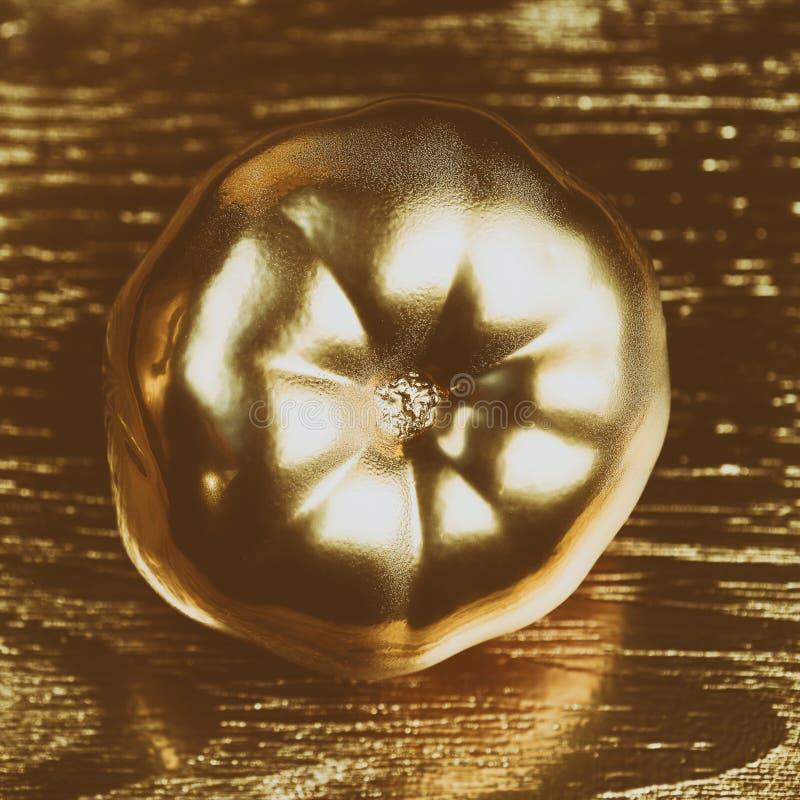 Guld- tomat på guld- träbakgrund tonat foto arkivbilder