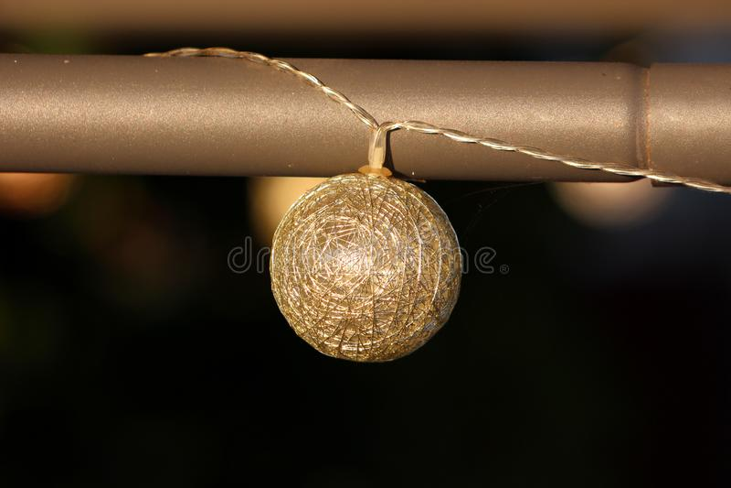 Guld- trådjul klumpa ihop sig prydnaden med inre LETT ljus som hängs från partiet för trädgården för metallpolen det väntande på fotografering för bildbyråer