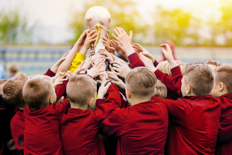 Guld- trofélönelyft BarnfotbollTeam Raising Golden Winning Football trofé royaltyfri bild