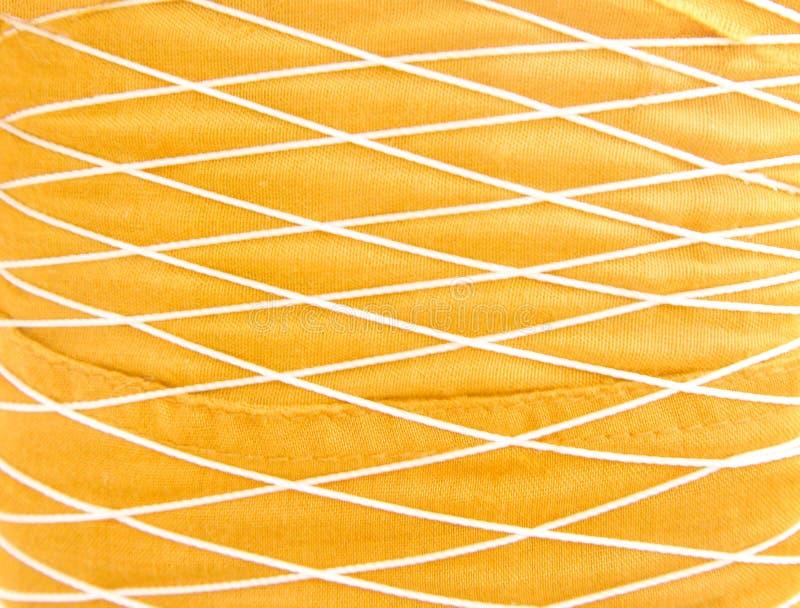 Guld- tygbakgrund med flätar samman av trådmodelltextur arkivbilder