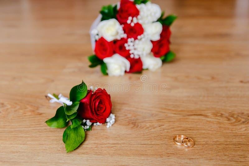 Guld- vigselringar, brudgums boutonniere och bruds bukett av röda och vita rosor på en träbakgrund br?llop arkivbilder