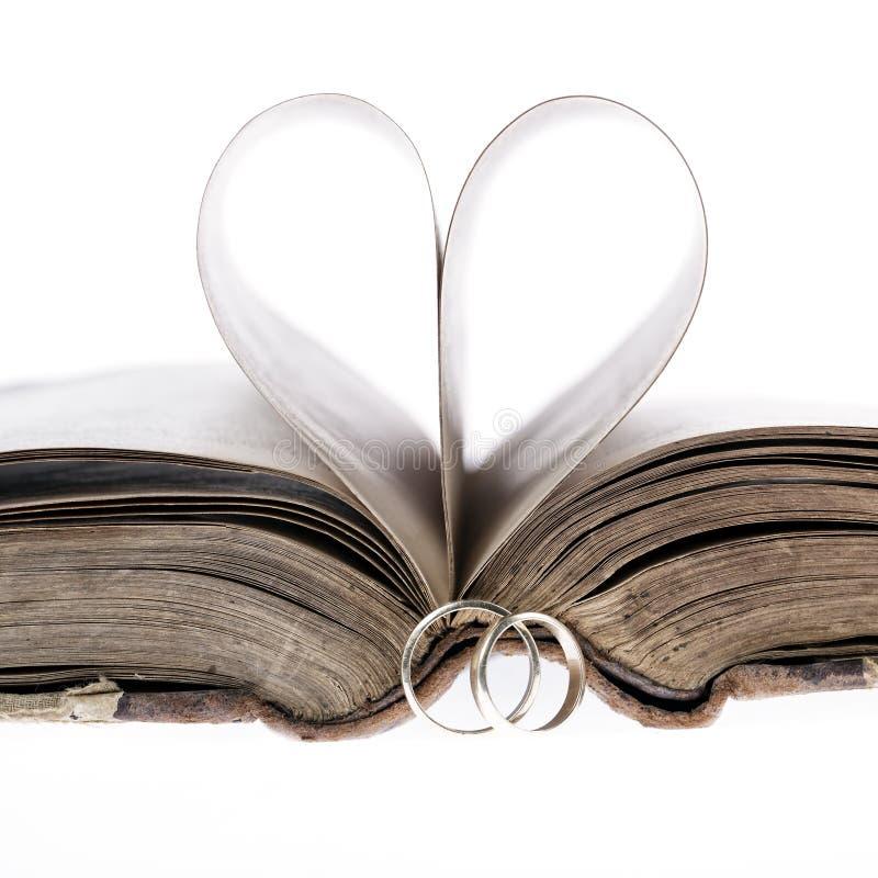 Guld- vigselringar, gammal bok och pappershjärta royaltyfri fotografi