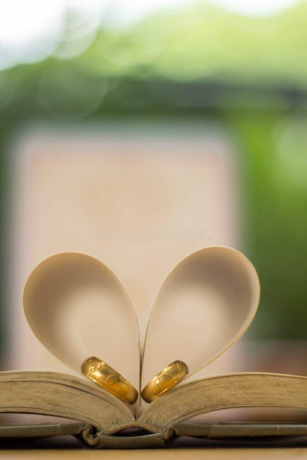 Guld- vigselringar, hjärtabok, bakgrundssuddighet arkivbild