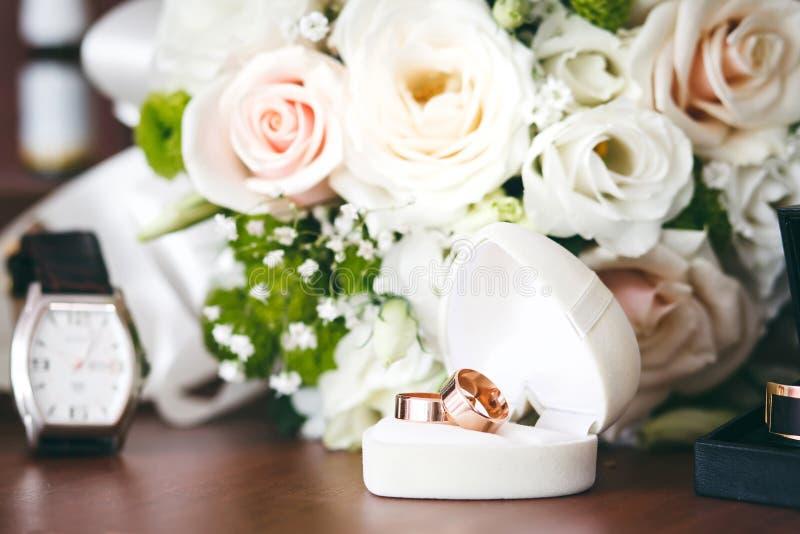 Guld- vigselringar i den vita gåvaasken med buketten och klocka i bakgrund royaltyfria bilder