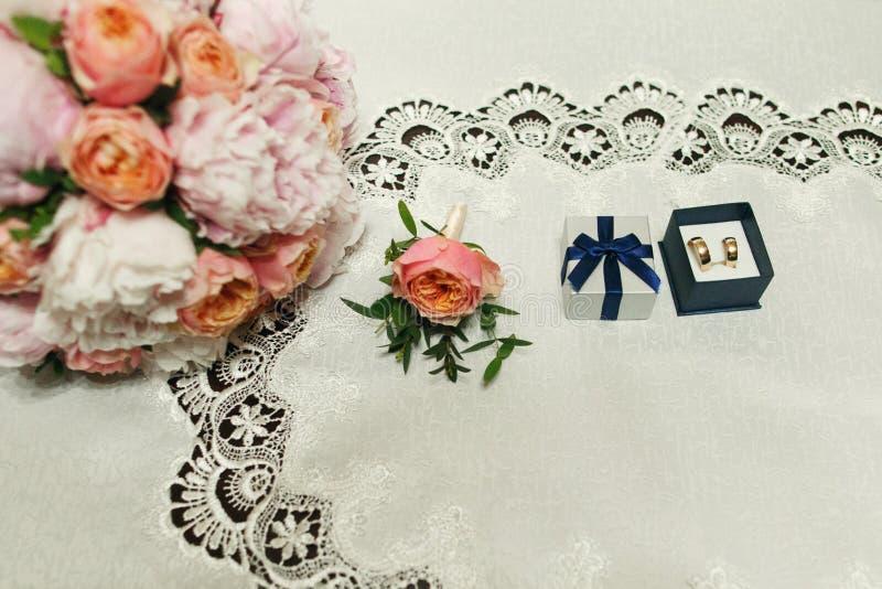 Guldbröllopcirklar i en ask med bandet och rosa bukettslut royaltyfria foton