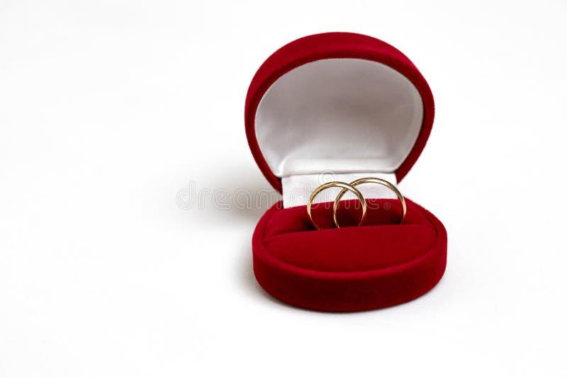 Guldbröllopcirklar i en röd gåvaask arkivbilder