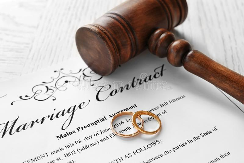 Guldbröllopcirklar med domareauktionsklubban på förbindelseavtal royaltyfria foton