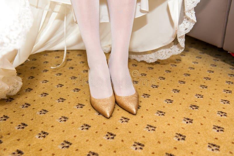 Guldbröllopskor på brudfot royaltyfria foton