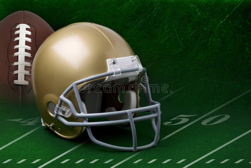 Guldfotbollhjälm och fotboll på grönt fält fotografering för bildbyråer