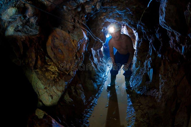 guldgruvarbetare som passerar den strama tunnelen royaltyfri foto