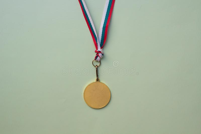 guldmedalj på ett mångfärgat band på en grön bakgrund arkivfoton