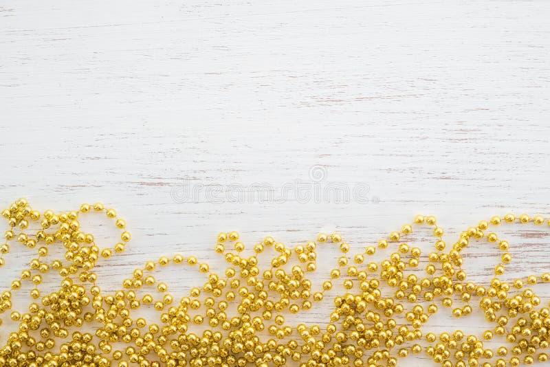 Guldpärlor för julgran på vitt trä arkivfoto