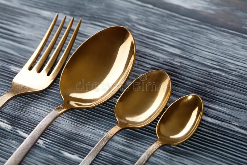 Guldskedar och gaffel på den gråa träbakgrunden tappningbordsservis med skrapatunt smörlager slapp fokus Moget frö av granatäpple arkivbild