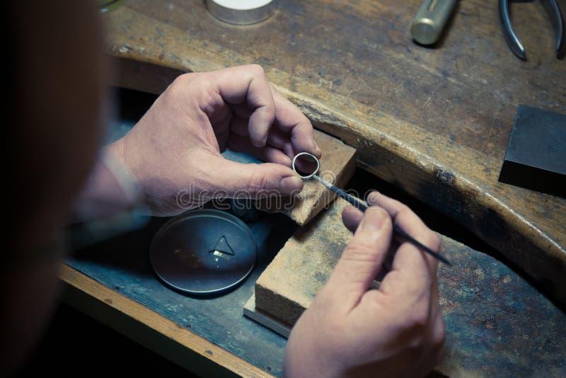 Guldsmed som arbetar på vigselringen royaltyfria foton