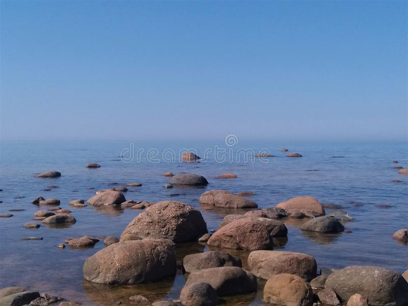 Gulf of Finland, cold northern Baltic Sea, Finland. The beauty of the northern summer. Sea, beach, large stones, horizon. Calm, royalty free stock image