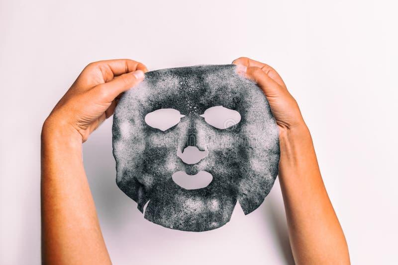 Gulgocze maskowej kobiety robi twarzowemu piękna traktowaniu z węgla drzewnego detox purifying pores produktu mienia produktem pr fotografia royalty free