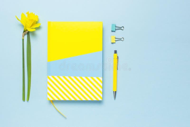 Guling-bl?tt anteckningsbok, penna, gem, pingstlilja f?r v?rblommap?skliljor p? bl? bakgrund Kvinnligt skrivbord, kontorsskrivbor royaltyfria foton