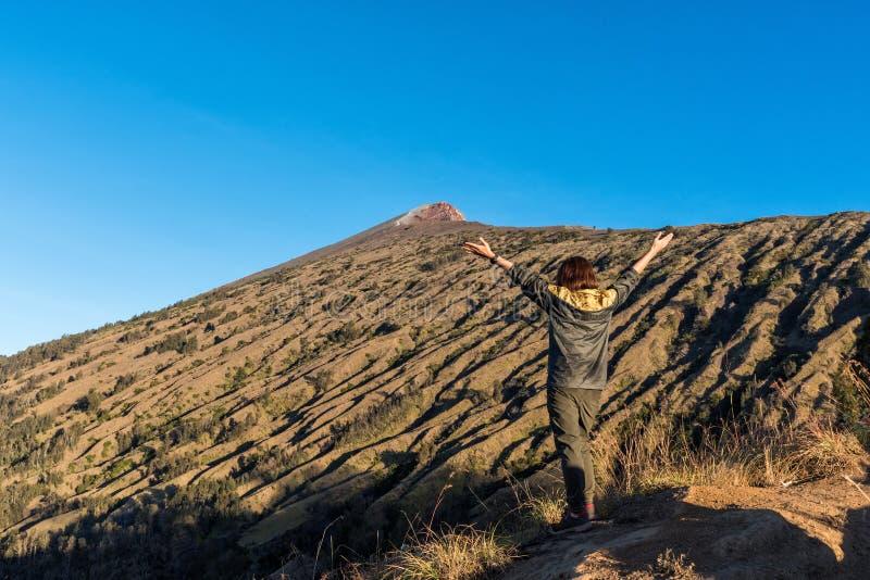Guling för kvinnafotvandrarekläder tillbaka klår upp och att fördela handen, tycker om och lyckligt med bästa sikt för berg efter royaltyfri fotografi
