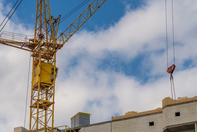 Guling för tornkranen tar byggnadsmaterialen till konstruktionen av mång--våningen huset royaltyfria bilder