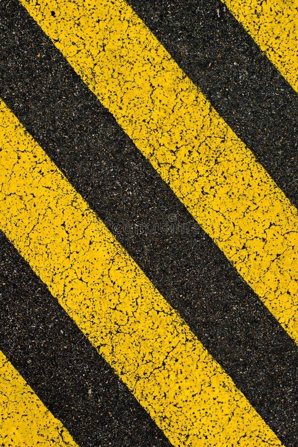 Guling gjorde randig vägteckning på svart asfalt. royaltyfri foto