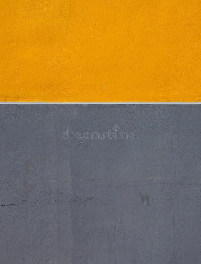 Guling och gråzoner av målarfärg på en grov texturerad betongvägg som delas av ett horisontalvitt band royaltyfri bild