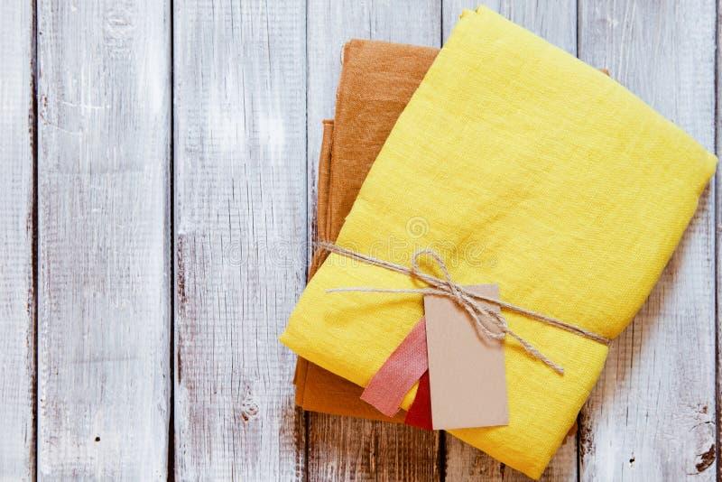 Guling- och ockralinnetyg som packas med juterepet Begrepp av att sy fr?n naturlig textilkl?dbakgrund royaltyfria foton