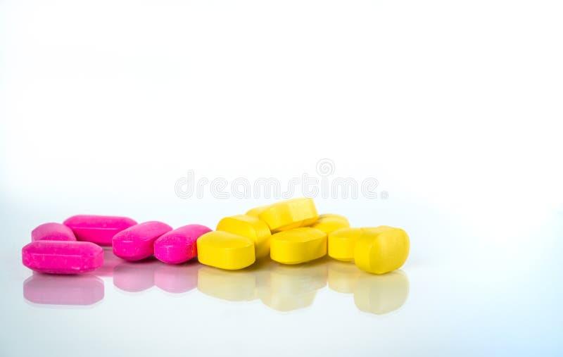 Guling och rosa ovala minnestavlapreventivpillerar med skuggor på vit bakgrund med kopieringsutrymme för text Milt att dämpa smär arkivfoton