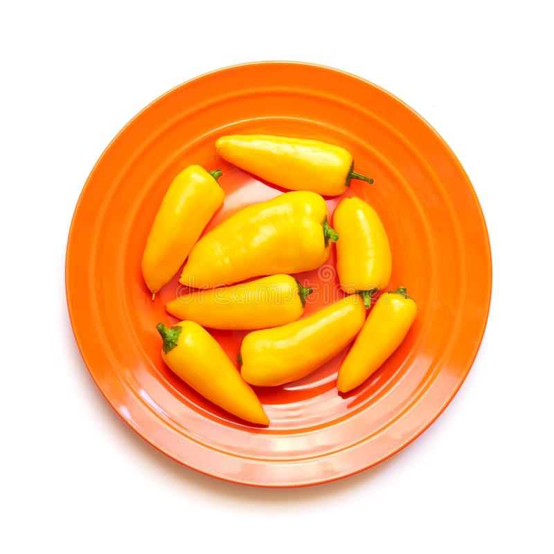 Gulingpeppar på den orange plattan som isoleras på vit royaltyfri bild