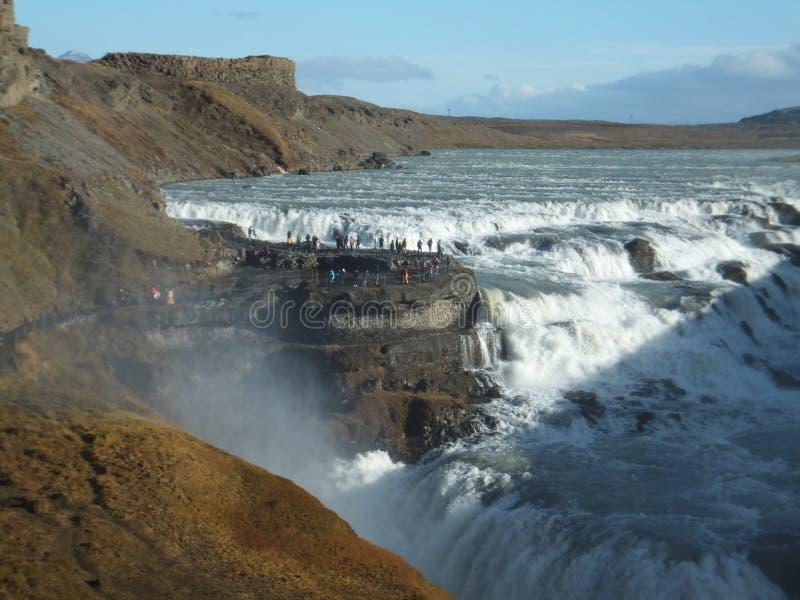 Gullfoss in Island an einem sonnigen Tag, mit kleinen Zahlen von den Leuten, die es bewundern lizenzfreies stockfoto