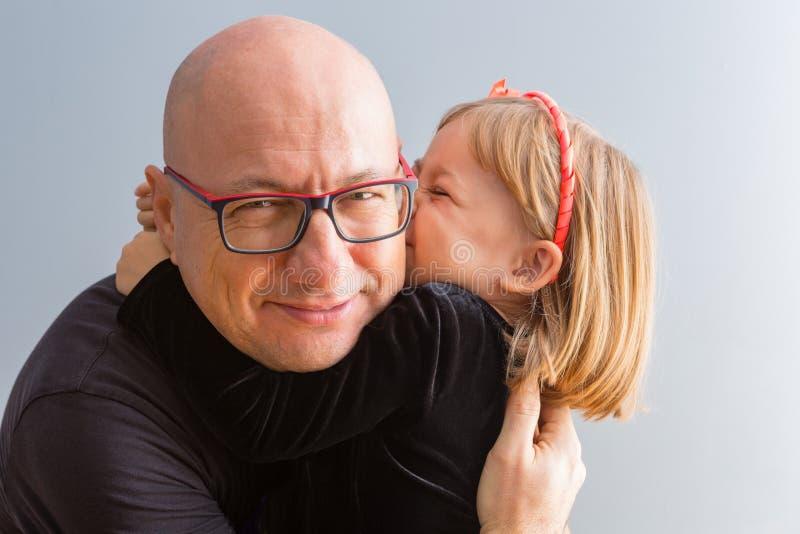 Gullig älska liten flicka som kysser hennes pappa arkivfoton