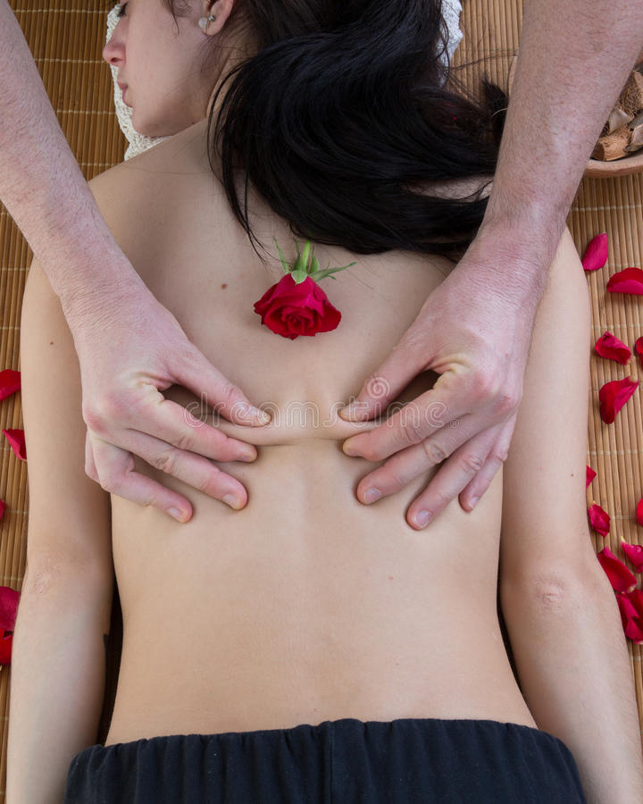 Gullig älskvärd flicka som får en tillbaka massage på en brunnsort royaltyfri bild