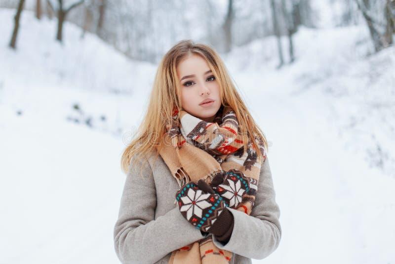 Gullig älskvärd ung kvinna i ett stilfullt vinterlag i woolen tappningtumvanten med en woolen beige halsduk med enfärgad modell royaltyfri fotografi