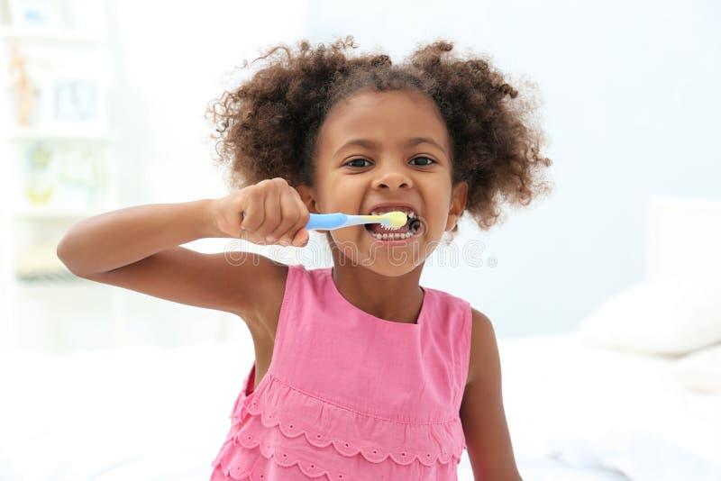 Gullig afrikansk amerikanflicka som borstar tänder i badrum arkivbild