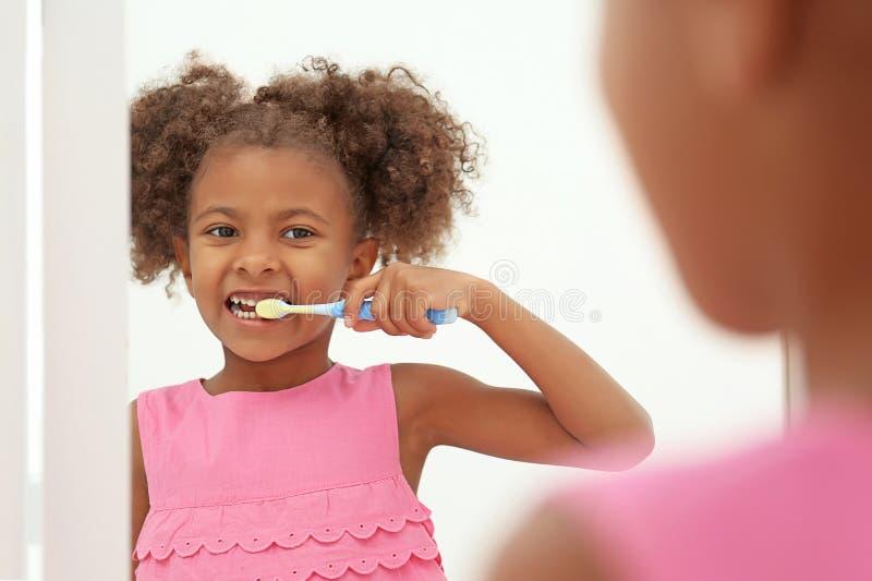 Gullig afrikansk amerikanflicka som borstar tänder och ser i spegel i badrum royaltyfri bild