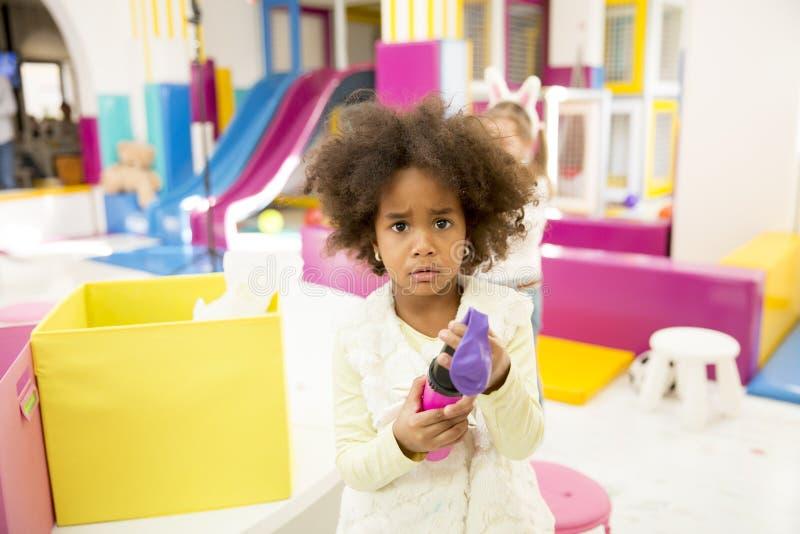 Gullig afrikansk amerikanliten flicka i lekrum fotografering för bildbyråer