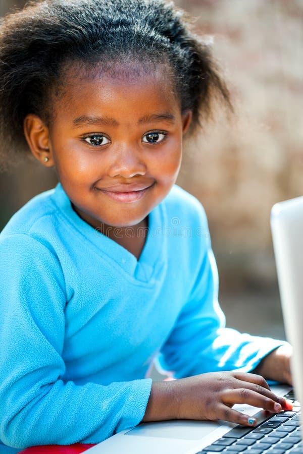 Gullig afrikansk flickamaskinskrivning på bärbara datorn royaltyfri foto