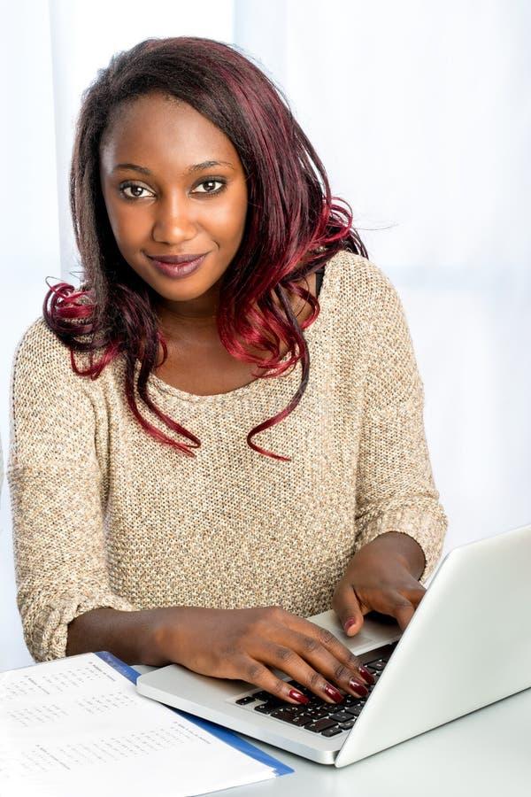 Gullig afrikansk tonårig flickamaskinskrivning på bärbara datorn arkivbild
