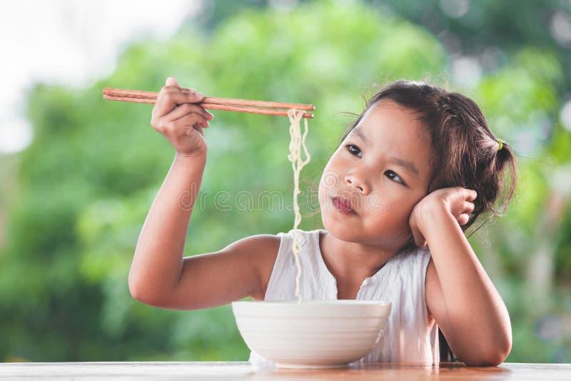 Gullig asiatisk barnflicka som borras för att äta ögonblickliga nudlar royaltyfria foton